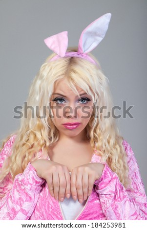 Beautiful young blond woman as easter bunny with rabbit ears on / costume / carneval - stock photo