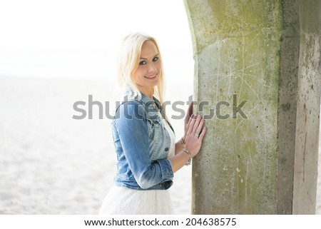 Beautiful young blond woman at the seaside wearing a blue top and white skirt posing holding a stone pier support backlit by the bright sun, with copyspace - stock photo