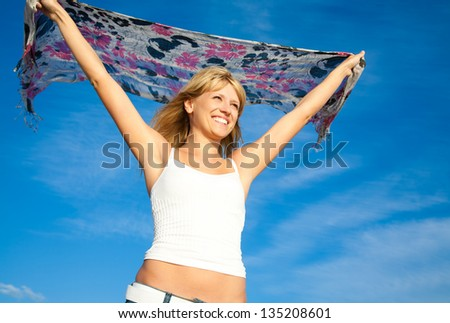 beautiful young blond woman dancing with kerchief against the blue sky