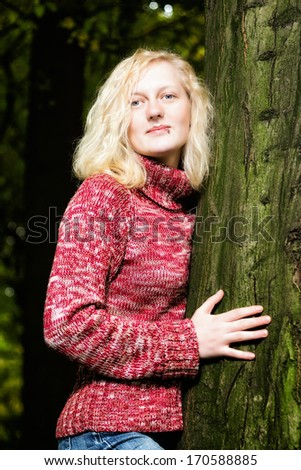 Beautiful young blond woman daydreaming at night standing outdoors against a tree, she is illuminated - stock photo