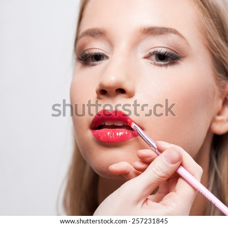 Beautiful young blond woman getting her makeup. - stock photo