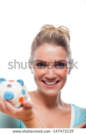 Beautiful young blond woman holding a colourful polka dot piggy bank in her hand smiling in anticipation of realising her goals and dreams isolated on white