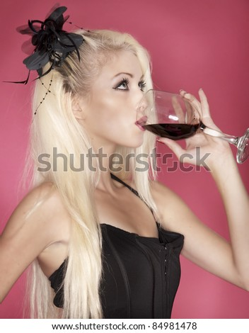 Beautiful young blond woman holding and drinking a glass of red wine - stock photo