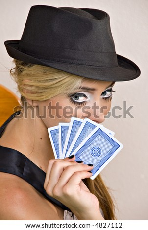 beautiful young blond woman holding playing cards near face and wearing black hat