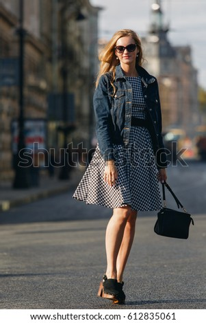 beautiful young blond woman in a black and white dress and denim jacket standing in the middle of the street and smiles, the sun shines