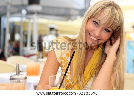 beautiful young blond woman in a cafe with a glass of juice