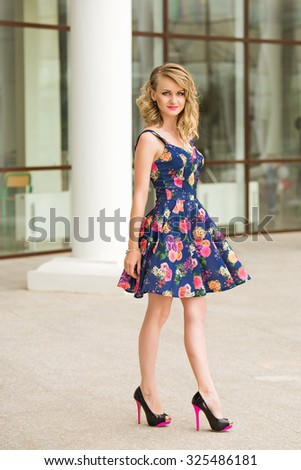beautiful young blond woman in a flowered dress with heels