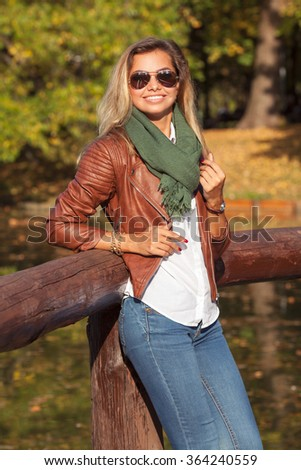 Beautiful young blond woman in a park  - stock photo