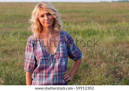 Beautiful young blond woman in a plaided dress in the summer meadow - stock photo