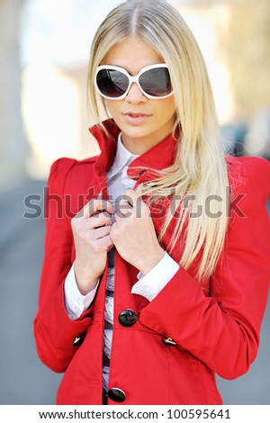 Beautiful young blond woman in a red dress and sunglasses backlit - stock photo