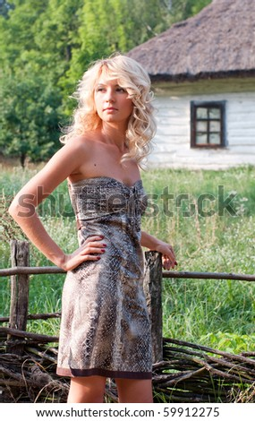 Beautiful young blond woman in rural area near wooden house