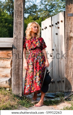 Beautiful young blond woman in rural area standing in the wooden gate barefoot - stock photo