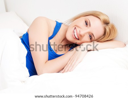 beautiful young blond woman in the bed at home - stock photo