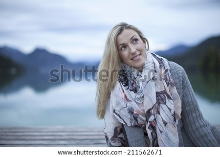 Beautiful young blond woman in winter fashion with an elegant scarf draped over her overcoat standing outdoors at a mountain lake looking up thoughtfully into the air - stock photo
