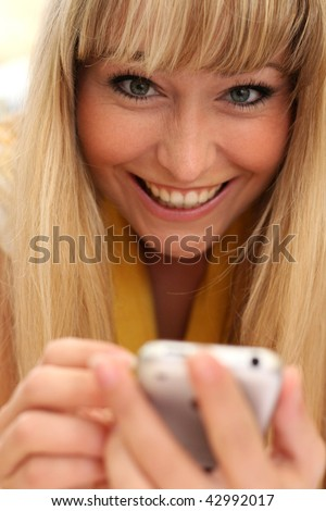beautiful young blond woman is very glad with her cell phone