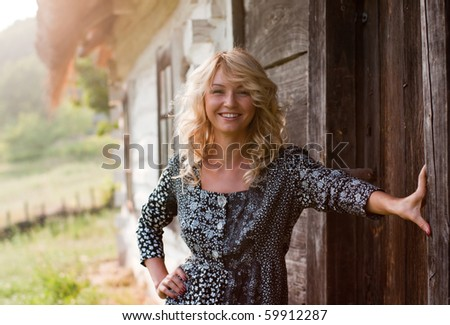 Beautiful young blond woman near old country house smiling in the sunset light - stock photo