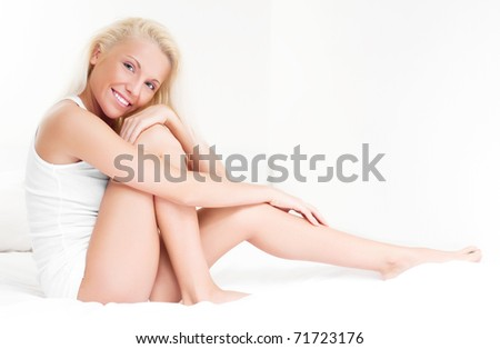 beautiful young blond woman on the bed at home - stock photo