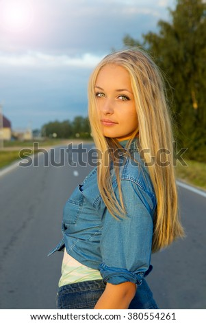 beautiful young blond woman on the road  - stock photo