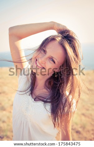 Beautiful young blond woman outdoors portrait. Beautiful young blond woman street portrait. it is dressed in white dress. hair develop on a wind - stock photo