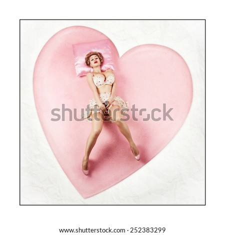 Beautiful young blond woman pin-up in stockings on a pink pillow on a white background - stock photo