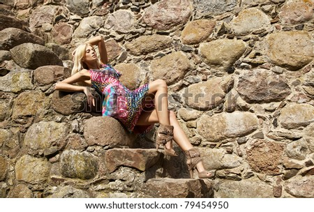 Beautiful young blond woman pose near medieval castle. - stock photo