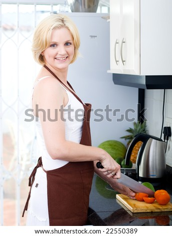 Beautiful young blond woman preparing food in the kitchen - stock photo
