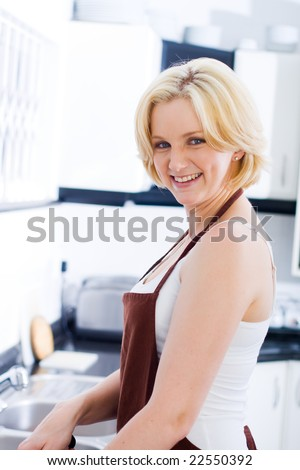 Beautiful young blond woman preparing food in the kitchen