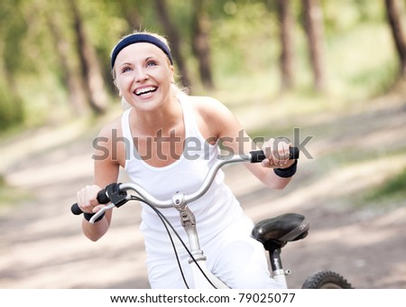 beautiful young blond woman  riding a bicycle on a warm summer day