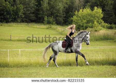 Beautiful young blond woman riding a horse in summer meadow