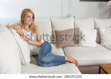 Beautiful young blond woman sitting and relaxing on a white sofa at home, smiling and lounging in a stylish and elegant living room, luxury spacious home interior. Aspirational lifestyle, indoors.