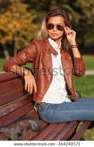 Beautiful young blond woman sitting on a bench in a park - stock photo