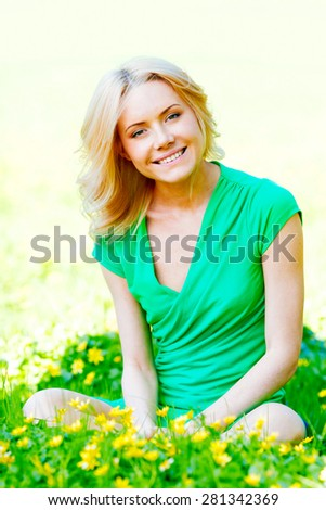 Beautiful young blond woman sitting on grass in park and enjoyng flowers - stock photo