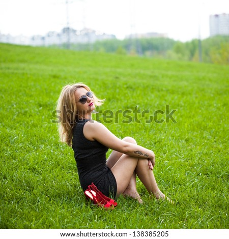 beautiful young blond woman sitting on the grass. In sunglasses, a black dress, barefoot.