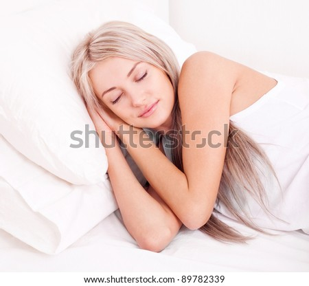 beautiful young blond woman sleeping in  bed at home - stock photo