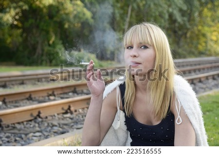 beautiful young blond woman smoking cigarette - stock photo