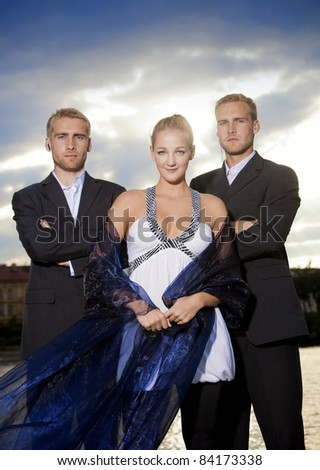 beautiful young blond woman standing outdoors accompanied by two bodyguards - stock photo