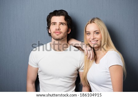 Beautiful young blond woman standing smiling at the camera and leaning on her husbands shoulder as he stares pensively up into the air - stock photo