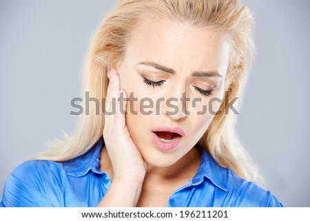 Beautiful young blond woman suffering from toothache holding her hand to a jaw as she stands frowning in pain with her mouth open - stock photo