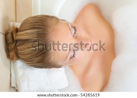Beautiful young blond woman taking bath - stock photo