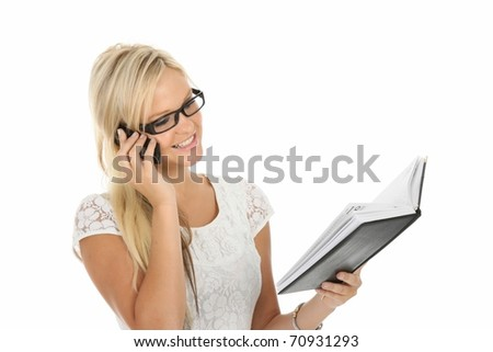 Beautiful young blond woman talking on mobile phone and checking her diary - stock photo