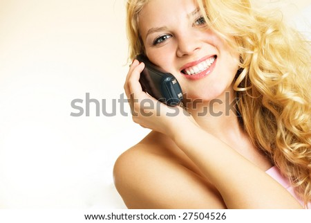 beautiful young blond woman talking on the phone and laughing - stock photo