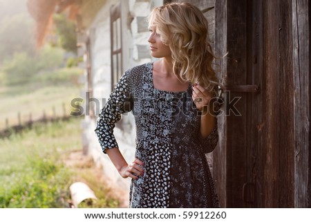 Beautiful young blond woman thoughtfully standing near old country house in the sunset light - stock photo