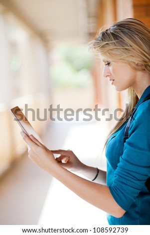 beautiful young blond woman using tablet computer - stock photo