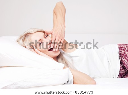 beautiful young blond woman waking up, yawning and stretching on the bed at home - stock photo