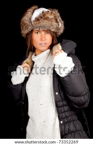 beautiful young blond woman wearing a warm winter hat and black coat, black background