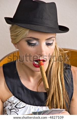 beautiful young blond woman wearing black hat holding playing cards with cigar in mouth - stock photo