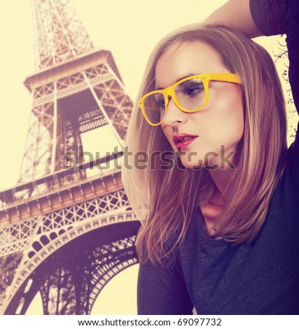 beautiful young blond woman wearing fashionable yellow glasses against Eiffel Tower in Paris with cross-processed effect. - stock photo