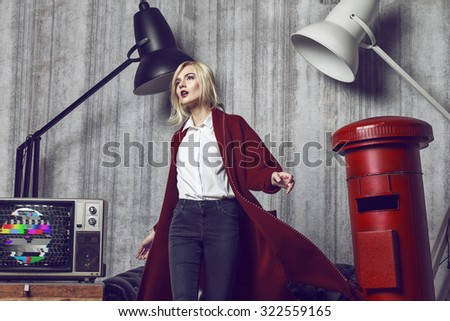 Beautiful young blond woman wearing long red coat. Her hair is tied into fashion ponytail and fresh natural make up suit to the style. Composition is fill with black and white lamp,sofa and retro tv - stock photo
