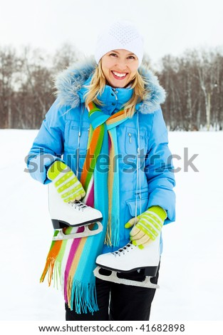 beautiful young blond woman wearing warm winter clothes going to ice skating - stock photo