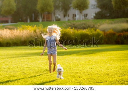 beautiful young blond woman with a dog breed lap dog running on the lawn in the park - stock photo